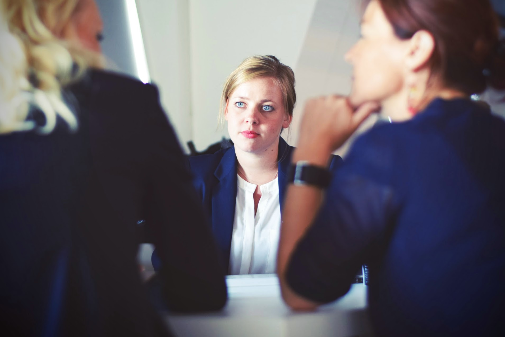 Woman in an interview with two other women conducting it