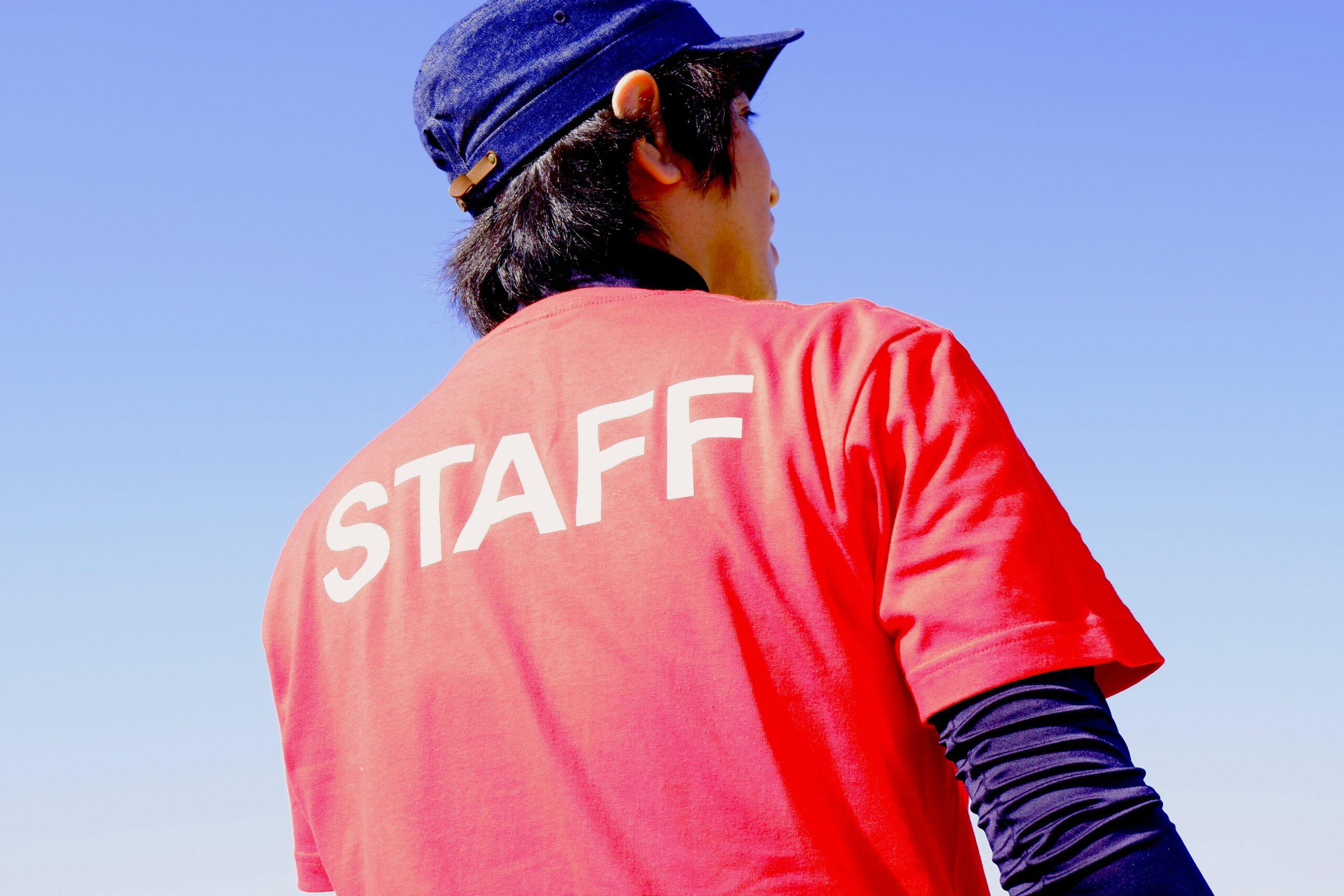 Man wearing a red Staff shirt