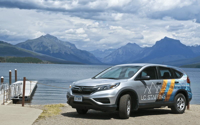 LC Staffing Logo car on the shore of a lake with mountains in the background