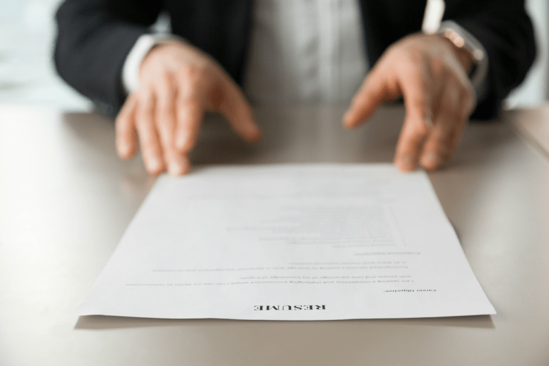 Close up of a man sliding a resume across a table